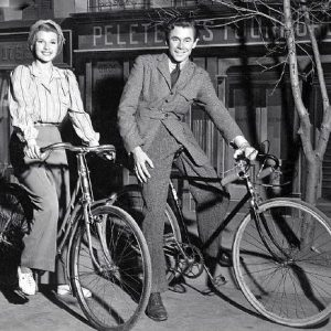"Rita Hayworth and Glenn Ford ride bikes. Look here in our archive for another image of Ford and Hayworth – the photo that launched ""Rides a Bike"" way-back-when!"