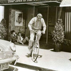 Danny Kaye rides a bike.