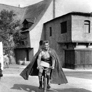 George Nader rides a bike.