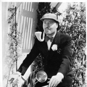 Jack Oakie rides a bike.
