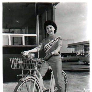 Annette Funicello rides a bike.