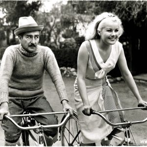 Adolphe Menjou and Joan Marsh ride bikes.