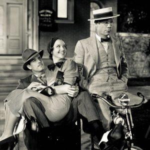 Joe E. Brown rides a bike. Maxine Doyle and Gordon Wescott ride a sidecar.
