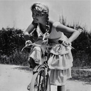 Brigitte Bardot rides a bike.