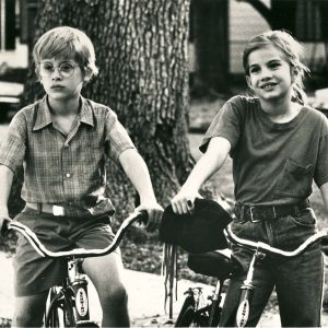 Macaulay Culkin and Anna Chlumsky ride bikes.