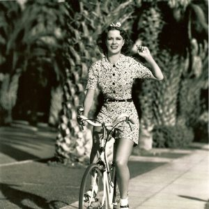 Eleanor Powell rides a bike.