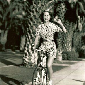 Eleanor Powell rides a bike.