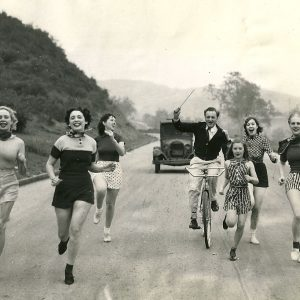 Ralph Thomas rides a bike, and wields a baton. Elaine Dennis, Helene Le Berthon, Colleen McWard, Marilyn Knowlden, Muriel Goodspeed and Eleanor Prentice run – and sing.