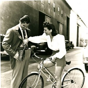 Joan Crawford rides a bike. And plays with Clark Gable's gun.