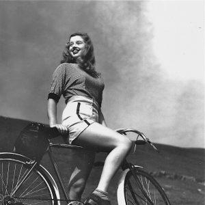 Diana Dors rides a bike.