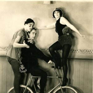David Newell, Richard Arlen and Kay Francis ride a bike.