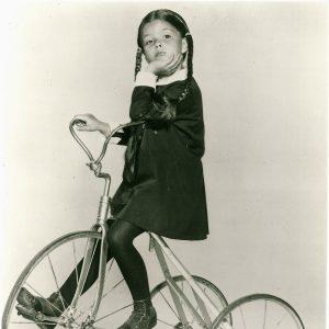 Lisa Loring rides a trike.