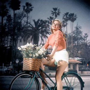 Anita Ekberg rides a bike. With flowers.
