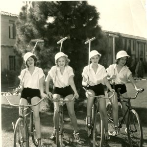 Ruth Hall, Shirley Chambers, Mae Madison and Geraldine Barton ride bikes, and wield polo mallets.