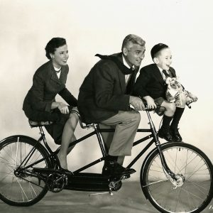 Laraine Day, Jeff Chandler, Tim Hovey and toy tiger ride a bike.