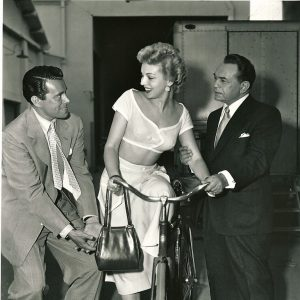 Kathleen Hughes mounts a bike. John Forsythe and Edward G. Robinson lend a hand.
