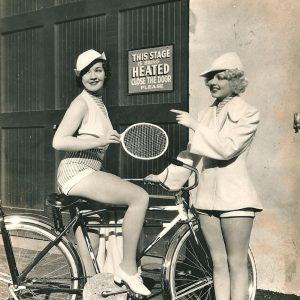 Louise Allen rides a bike, holds a racket. Victoria Vinton points.