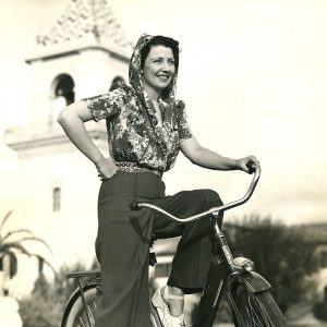 Barbara Jo Allen rides a bike. In hooded slack suit.