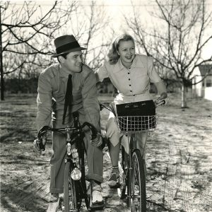 Dick Baldwin and Cecilia Parker ride bikes.