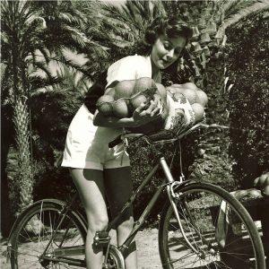 Rhonda Fleming rides a bike. With grapefruits.