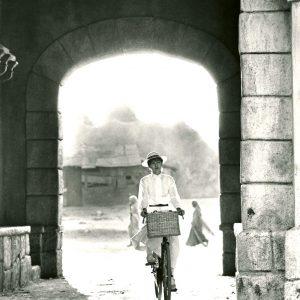Judy Davis rides a bike.