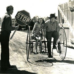 Lynn Roberts and Smiley Burnette ride a society bike.