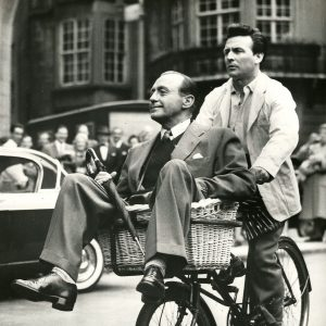 Jack Benny and grocer ride a delivery bike. Snipe: LONDON: Penny-pinching comedian Jack Benny believes in squeezing his pence, too. He's shown arriving in a bicycle basket at London's Dorchester Hotel, looking as proud as if he were in a Rolls Royce. The delivery bike ride will be featured in films Benny is making for his U.S. TV show.