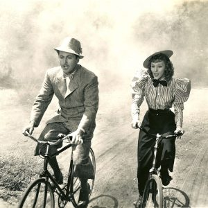 Allan Jones and Mary Martin ride bikes.