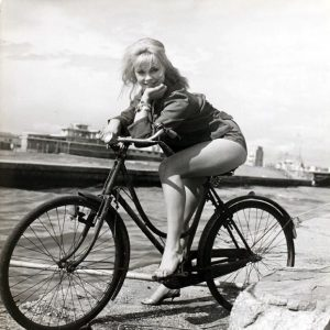 Elke Sommer poses on a bike.