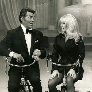 Dean Martin and Joey Heatherton ride trikes.