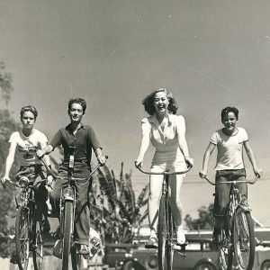 "Adele Mara and five ""youthful companions""  ride bikes."