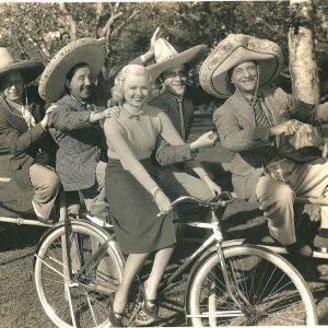 Busby Berkeley blond rides a bike. The Yacht Club Boys ride a fence.