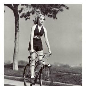 "Mary Beth Hughes rides a bike.""Keep that schoolgirl figure…and no better way is found than outdoor bicycling. So declares Mary Beth Hughes, Metro-Goldwyn-Mayer actress who makes her screen debut with Jeanette MacDonald in ""Broadway Serenade"".""Stiffening the legs with strong downward emphases on pedaling is a grand reducing exercise for thighs and hips. – May 9 1939"""
