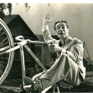 Joe E. Brown rides a bike. Wheelie-n'.