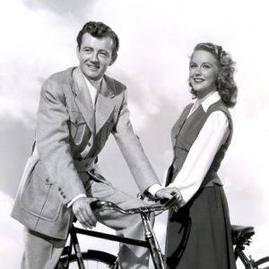 Robert Walker and Dorothy Patrick ride bikes.