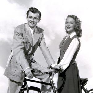 Robert Walker and Dorothy Patrick ride bikes.