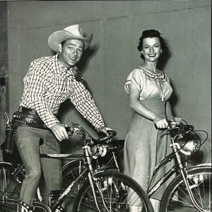 Roy Rogers and Dale Evans ride bikes.