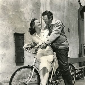 James Stewart and Peggy Dow ride a bike.
