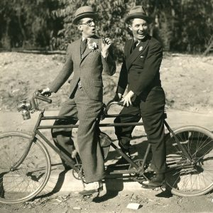 Bert Wheeler and Robert Woolsey ride a bike.