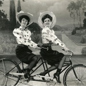Joan Davis and Constance Moore ride a bike.