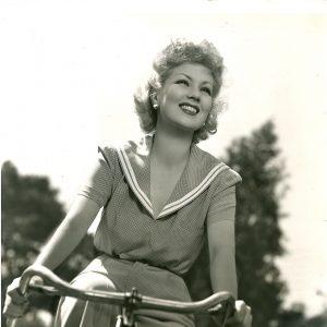 Ann Sothern rides a bike.
