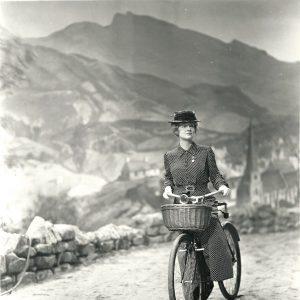 Bette Davis rides a bike.