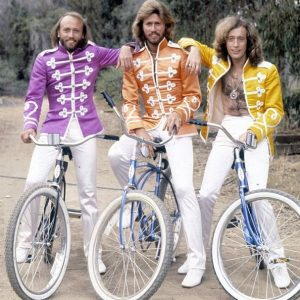 Barry, Maurice and Robin Gibb ride bikes.