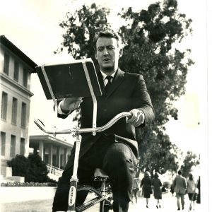 Tom Poston reads a bike.