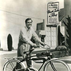 Joel McCrea walks a bike.