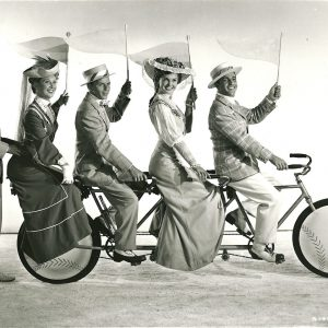 Betty Garrett, Frank Sinatra, Esther Williams and Gene Kelly ride a bike. Jules Munshin stands. Play ball!