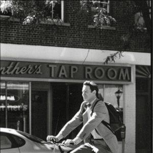 Kevin Kline rides a bike. Down Main Street in Northport, N.Y.