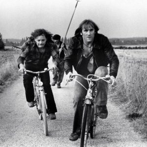Patrick Dewaere and Gerard Depardieu ride bikes.