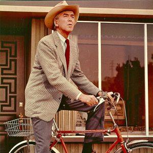 James Stewart rides a bike.