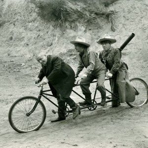Curly Howard, Larry Fine and Moe Howard ride a bike.